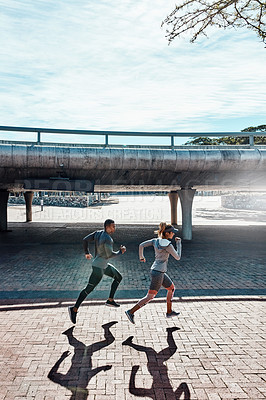 Buy stock photo Full length shot of two young and athletic young people running through the city