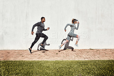 Buy stock photo Full length shot of two young and athletic young people running on a path through the park