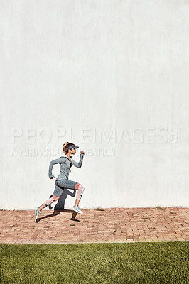 Buy stock photo Full length shot of an attractive and athletic young woman running on a path through the park