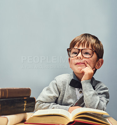 Buy stock photo Studio shot of a smart little boy reading books and looking thoughtful against a gray background