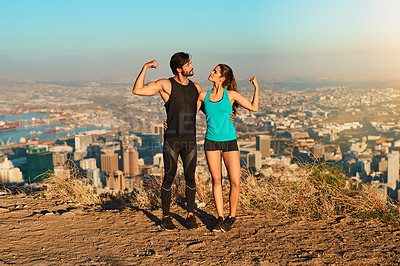 Buy stock photo Full length shot of a young couple flexing their muscles while out for a workout