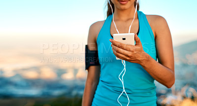 Buy stock photo Cropped shot of an unrecognizable young woman listening to music while out for a run