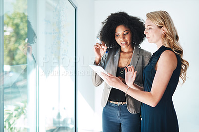 Buy stock photo Shot of two businesswomen using a digital tablet while brainstorming on a glass wall in an office