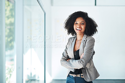 Buy stock photo Portrait of a young businesswoman standing with her arms crossed in an office