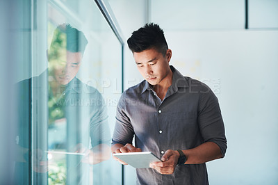 Buy stock photo Shot of a young businessman using a digital tablet in an office