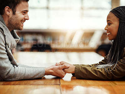 Buy stock photo Cropped shot of an affectionate young couple holding hands while sitting face to face at a table indoors