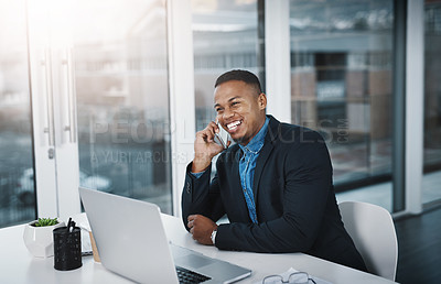 Buy stock photo Shot of a handsome young businessman talking on a cellphone while working in an office