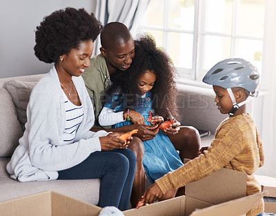 Buy stock photo Shot of a happy family unpacking boxes while moving house