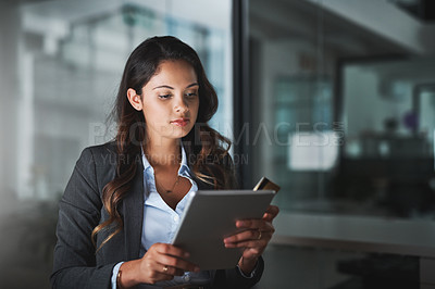 Buy stock photo Cropped shot of an attractive young businesswoman using her tablet to shop online while working late in the office
