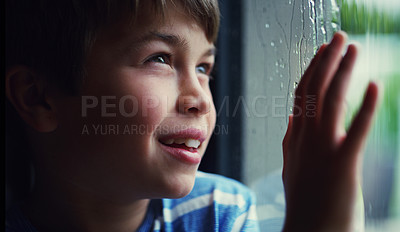 Buy stock photo Shot of a happy young boy watching the rain through a window at home