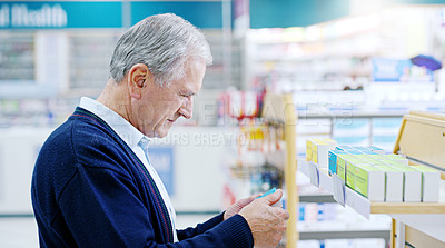 Buy stock photo Close up shot of a senior citizen deciding on which medicine to purchase at a pharmacy
