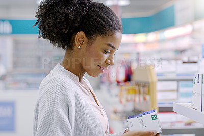 Buy stock photo Close up shot of an attractive young woman reading through the contents of a product at a pharmacy