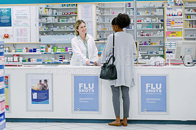 Buy stock photo Rearview shot of a young woman purchasing over the counter medication from a female pharmacist