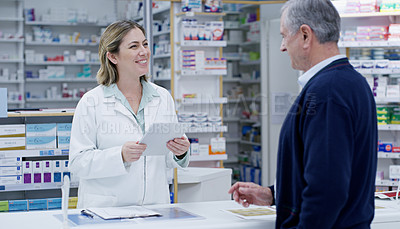 Buy stock photo Shot of a young pharmacist handing out a prescription to a senior citizen at a pharmacy