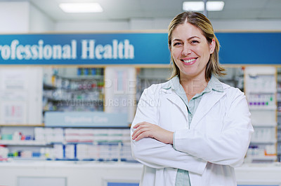 Buy stock photo Portrait of a young pharmacist smiling and posing with her arms folded in a pharmacy