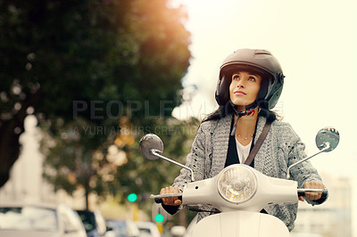 Buy stock photo Shot of an attractive young woman riding her scooter through the city