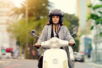 Buy stock photo Shot of an attractive young woman riding around the city on her scooter
