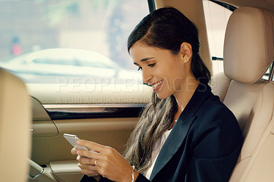 Buy stock photo Shot of an attractive young businesswoman using her cellphone inside a car while traveling to work