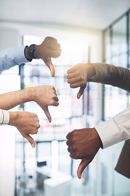 Buy stock photo Closeup shot of a group of businesspeople showing thumbs down in an office