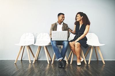 Buy stock photo Studio shot of a young businessman and businesswoman chatting in a waiting room