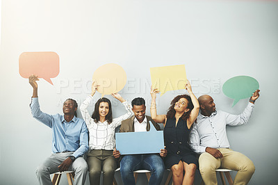 Buy stock photo Studio shot of a group of businesspeople holding colorful speech bubbles in line against a gray background