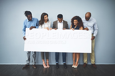 Buy stock photo Studio shot of a group of businesspeople holding a sign against a gray background