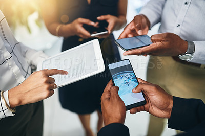 Buy stock photo Closeup shot of a group of businesspeople using digital devices in synchronicity in an office