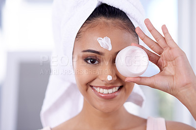 Buy stock photo Portrait of an attractive young woman applying moisturiser during her morning beauty routine