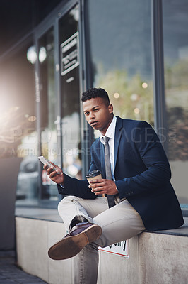 Buy stock photo Shot of a handsome young businessman using a cellphone while drinking coffee in the city