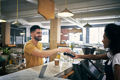 Buy stock photo Cropped shot of a handsome young man making payment to a female coffee shop employee