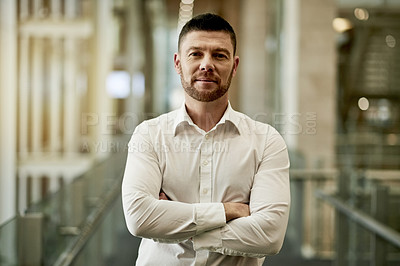 Buy stock photo Portrait of a mature businessman standing with his arms crossed in a modern office