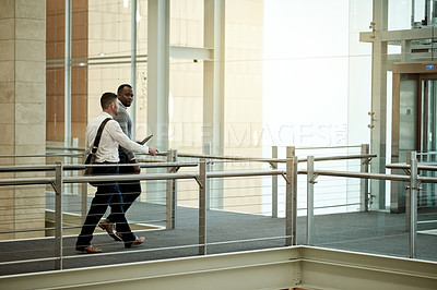 Buy stock photo Shot of two businessmen having a discussion while walking in a modern office