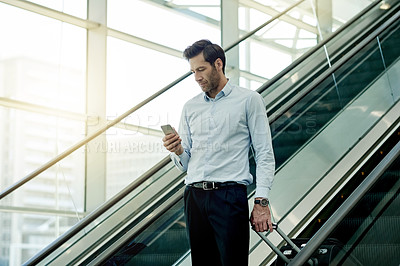 Buy stock photo Cropped shot of a young businessman using a cellphone while on an escalator