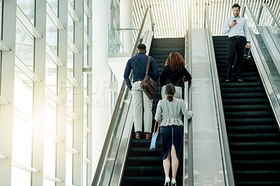 Buy stock photo Rearview shot of unrecognizable businesspeople going up an escalator in the workplace