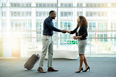 Buy stock photo Shot of businesspeople shaking hands in the workplace