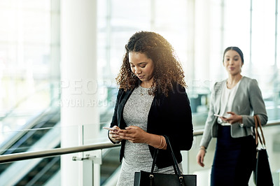 Buy stock photo Cropped shot of a young businesswoman using a cellphone in the workplace