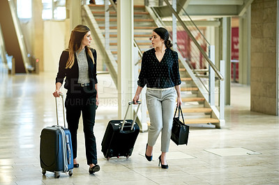 Buy stock photo Shot of two businesswomen walking through a convention center with their suitcases while on a business trip