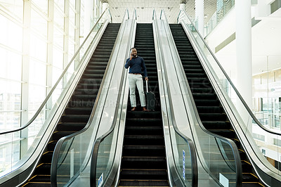 Buy stock photo Shot of a businessman on an escalator in the workplace