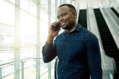 Buy stock photo Shot of a businessman talking on his cellphone while coming down the escalator