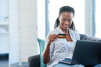 Buy stock photo Shot of a young woman using a credit card and laptop at home