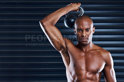 Buy stock photo Shot of a sporty young man working out with weights as part of his exercise routine