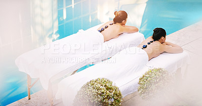 Buy stock photo High angle shot of two women getting hot stone massage at a spa