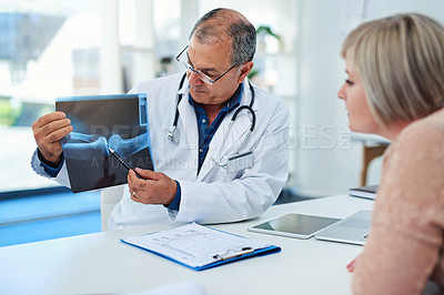 Buy stock photo Shot of a doctor discussing an x-ray scan with his patient