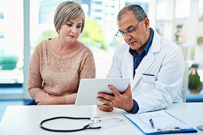 Buy stock photo Shot of a male doctor explaining something to his patient on his digital tablet