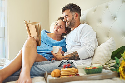 Buy stock photo Shot of an affectionate young couple relaxing in bed with a book and breakfast
