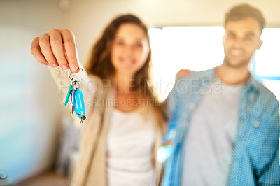 Buy stock photo Shot of a young couple holding the keys to their new home