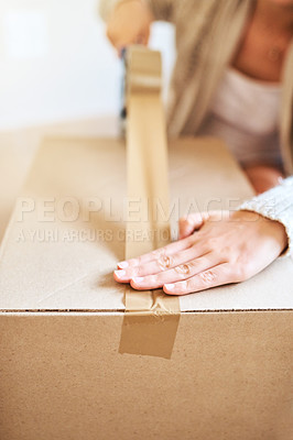 Buy stock photo Cropped shot of a young woman sealing a box while moving house