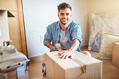 Buy stock photo Shot of a young man sealing a box while moving house
