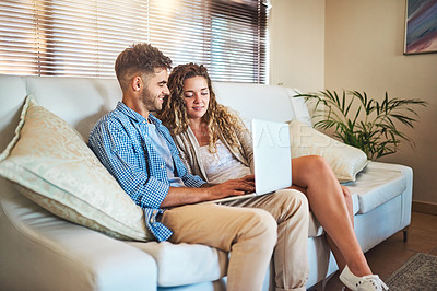 Buy stock photo Shot of a young couple using a laptop together on the sofa at home