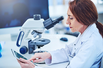 Buy stock photo Shot of a mature scientist using a digital tablet while conducting an experiment in a laboratory